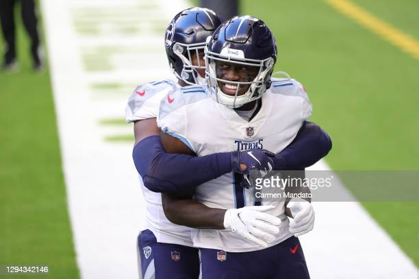 Brown of the Tennessee Titans celebrates a touchdown with Jonnu Smith during the first half against the Houston Texans at NRG Stadium on January 03,...