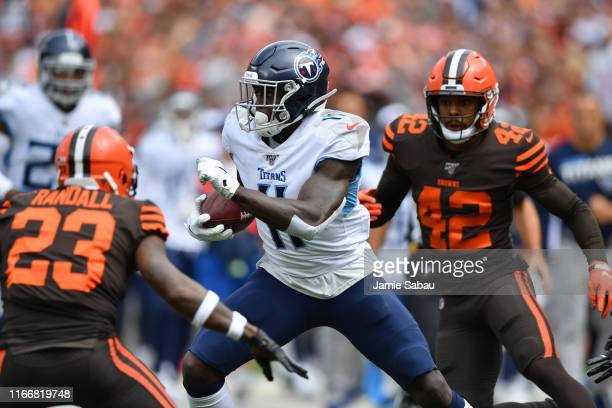 J Brown of the Tennessee Titans looks for running room in the first quarter as Damarious Randall of the Cleveland Browns and Morgan Burnett of the...