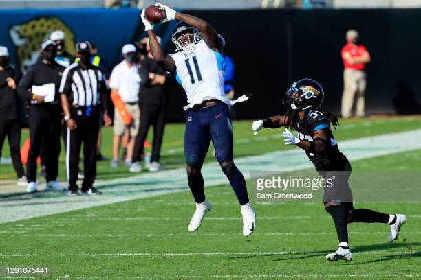 Brown of the Tennessee Titans makes a catch over Tre Herndon of the Jacksonville Jaguars at TIAA Bank Field on December 13, 2020 in Jacksonville,...