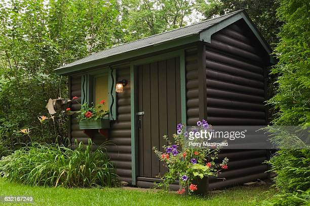 brown painted log garden shed with red geraniums in window box and orange daylilies and planter - shed stock pictures, royalty-free photos & images