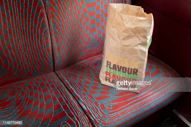 A brown paper bag containing the remnants of fast food from Burger King discarded on a seat in a London bus on 30th April 2019 in London England