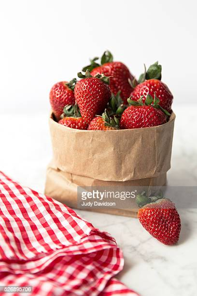 Brown paper bag full of fresh strawberries on white marble table