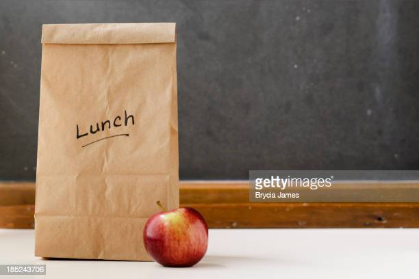 Brown paper lunch bag, red apple and chalkboard