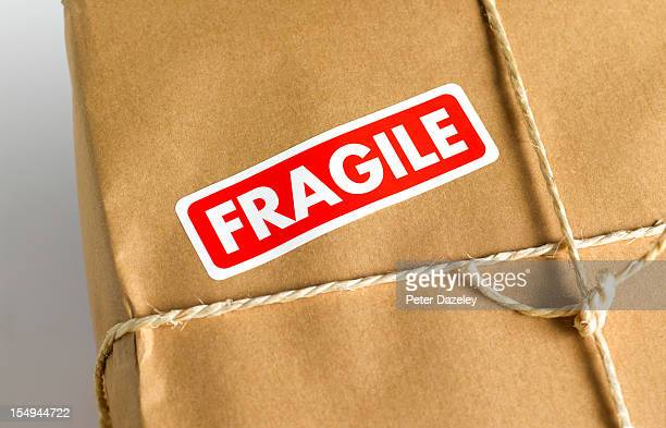 brown paper parcel with fragile sticker - fragile sign stock pictures, royalty-free photos & images