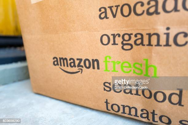 Brown paper tote for Amazon Fresh grocery delivery service with Amazon logo and text listing groceries which may be ordered using the service on the...