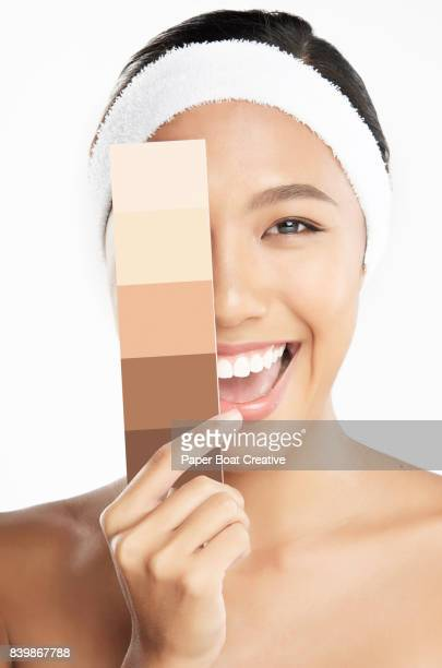 Brown skinned woman proudly shows off her skin while holding a skin tone palette