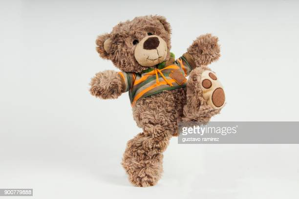 brown stuffed bear kicking - stuffed toy stock pictures, royalty-free photos & images
