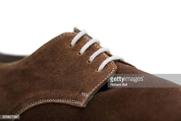 Brown suede shoe on a white background