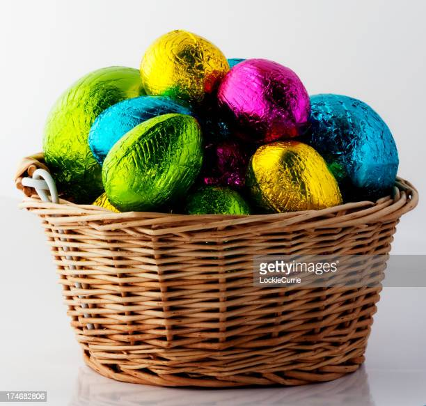 A brown wicker basket filled with shiny multicolor eggs