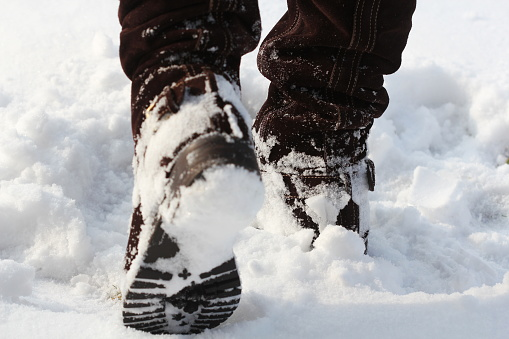 Brown women's shoes covered by snow in the winter 921559792