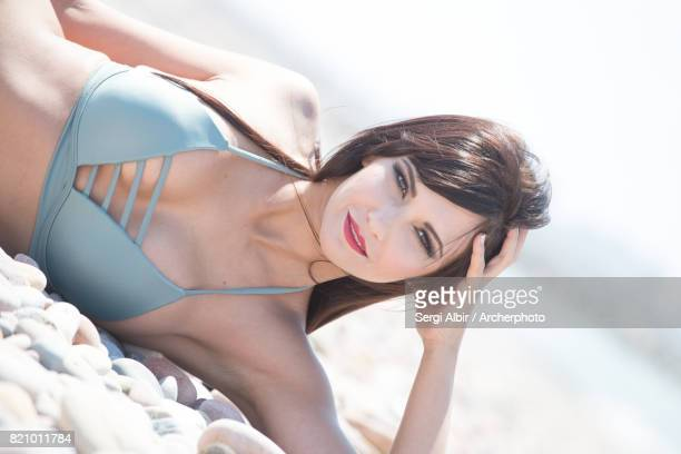 Brown-haired girl laying in a pebbles beach