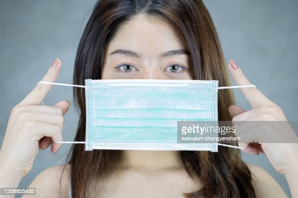 brown-haired girl with a medical mask on a gray background. - nurse mask stock pictures, royalty-free photos & images