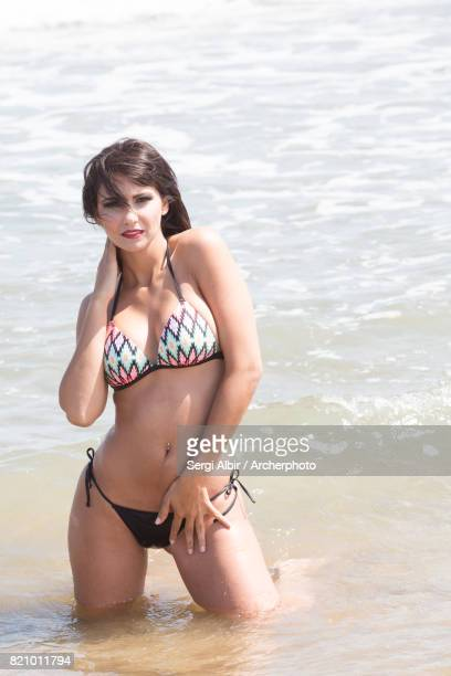 Brown-haired young woman in a colorful bikini kneeling in the sea