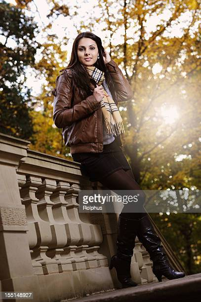 brown-haired young woman relaxing at old balustrade fall - brown jacket stock pictures, royalty-free photos & images