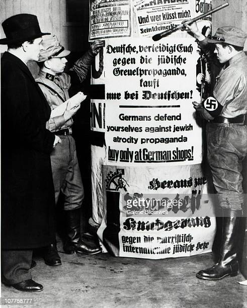 SA Brownshirts In Berlin Members of the SA Storm Division are pasting posters on an advertising column April 1933 The text says 'Germans defend...