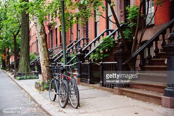 brownstone row houses and sidewalk in west village, new york city, usa - ニューヨーク ソーホー ストックフォトと画像