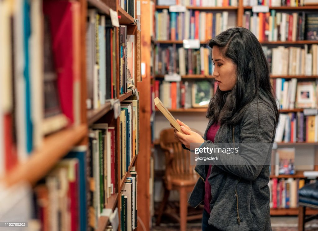 Browsing choices in a bookstore : Foto de stock