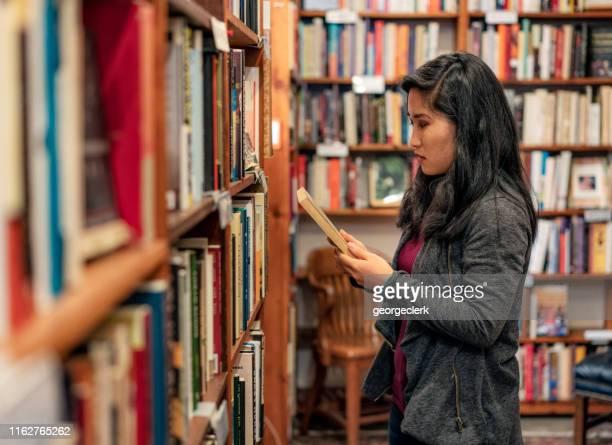 browsing choices in a bookstore - ver a hora imagens e fotografias de stock