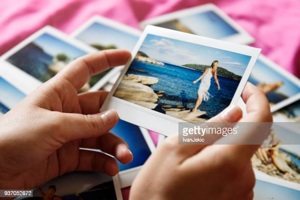 browsing vacation photographs at home - a closeup - photo album stock photos and pictures