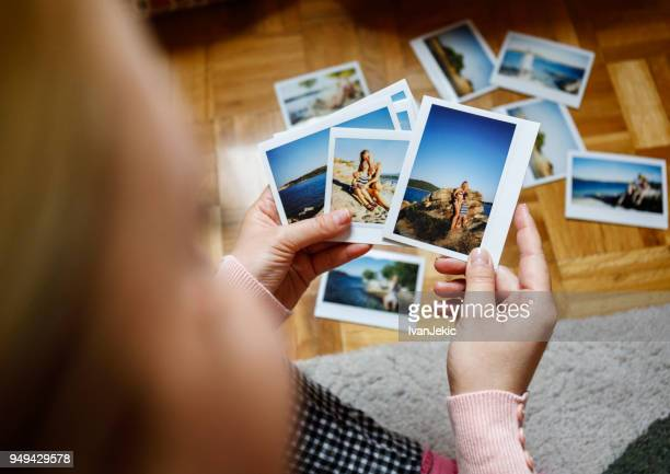browsing vacation photographs at home - photo album stock photos and pictures