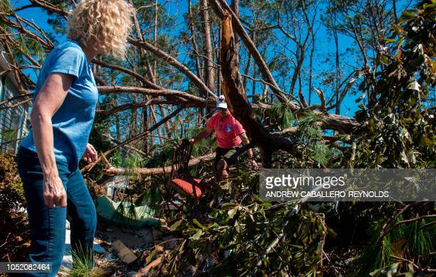 Bruce and Melissa Christensen collect chairs from a tree that fell on their house in Port St Joe Florida on October 13 three days after hurricane...