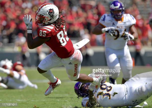 Bruce Bivens of the East Carolina Pirates attempts to tackle Keyon Lesane of the North Carolina State Wolfpack during the second half of their game...