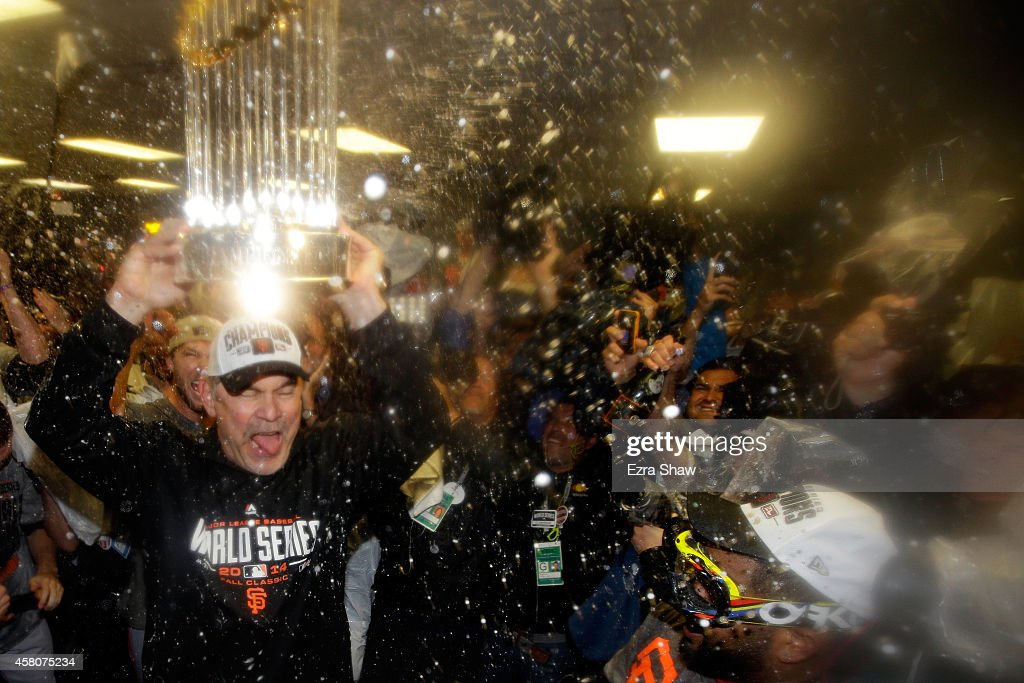 Bruce Bochy #15 of the San Francisco Giants celebrates with The Commissioner's Trophy in the locker room after a 3-2 win over the Kansas City Royals in Game Seven of the 2014 World Series at Kauffman Stadium on October 29, 2014 in Kansas City, Missouri.