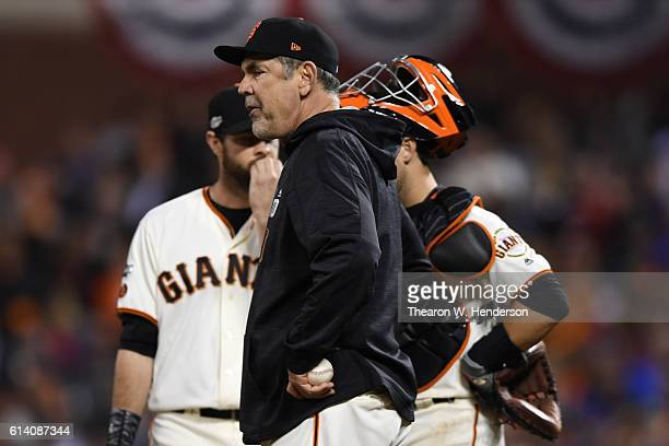 Bruce Bochy of the San Francisco Giants stands on the pitchers mound during a change in the ninth inning of Game Four of their National League...