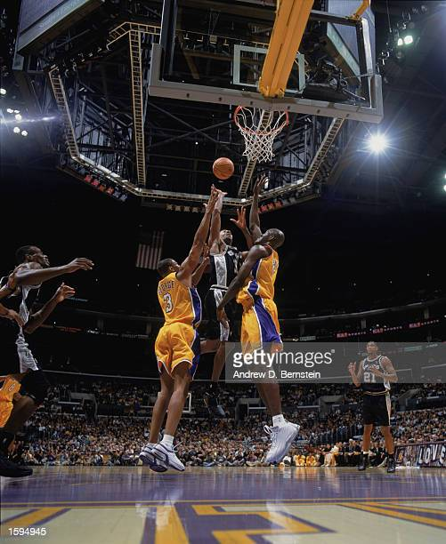 Bruce Bowen of the San Antonio Spurs shoots over Devean George and Soumaila Samake of the Los Angeles Lakers during the NBA game at Staples Center on...