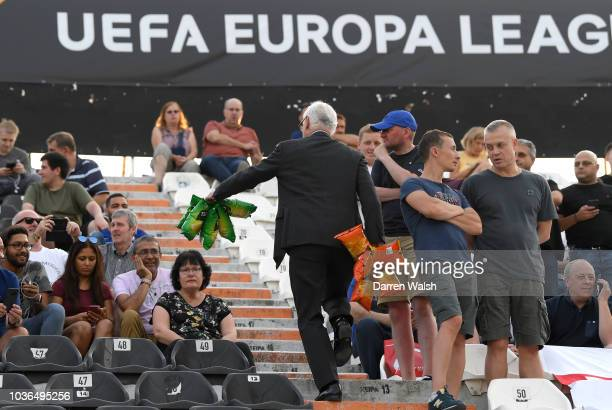Bruce Buck Chelsea chairman is seen handing out bags of crisps to Chelsea fans in the away stand prior to the UEFA Europa League Group L match...
