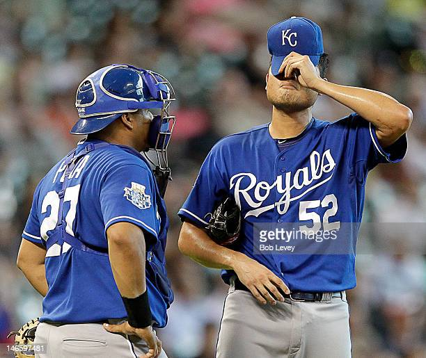 Bruce Chen of the Kansas City Royals pulls his hat down over his eyes as he talks to Brayan Pena of the Kansas City Royals before being taken out of...