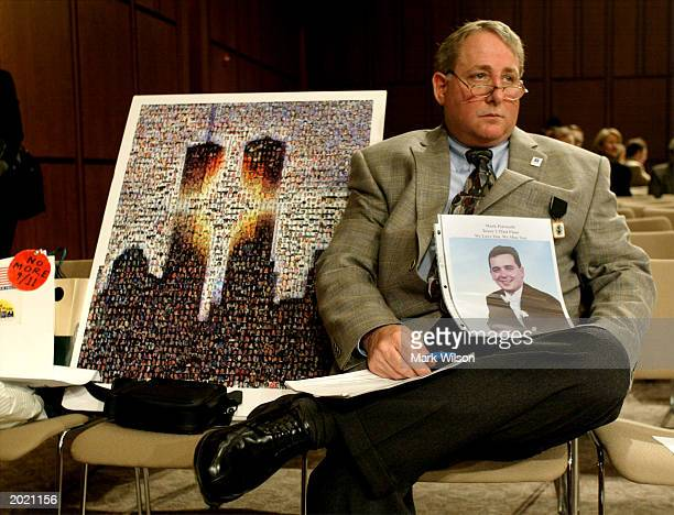 Bruce DeCell of Staten Island NY holds a photo of his soninlaw Mark Petrocelli while listening to testimony during a public hearing for the...