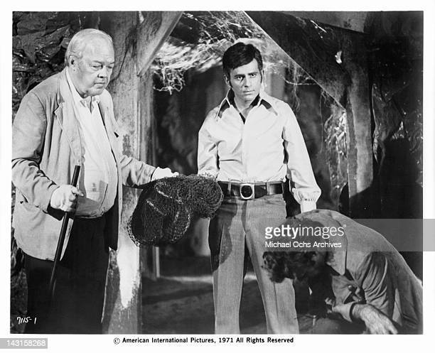 Bruce Dern crouching as Barry Kroeger and Casey Kasem follow the monster deep into the interior of the mine in a scene from the film 'The Incredible...