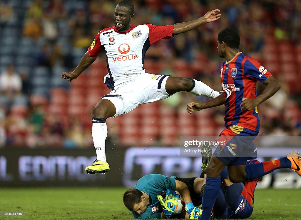 Bruce Djite of Adelaide United leaps over goalkeeper Ben Kennedy of the Jets during the round 27 A-League match between the Newcastle Jets and Adelaide United at Hunter Stadium on April 11, 2014 in Newcastle, Australia.