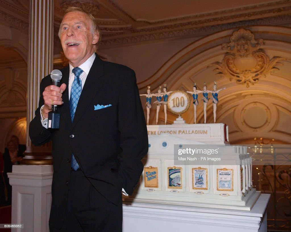 Bruce Forsyth speaks after cutting a commemorative cake