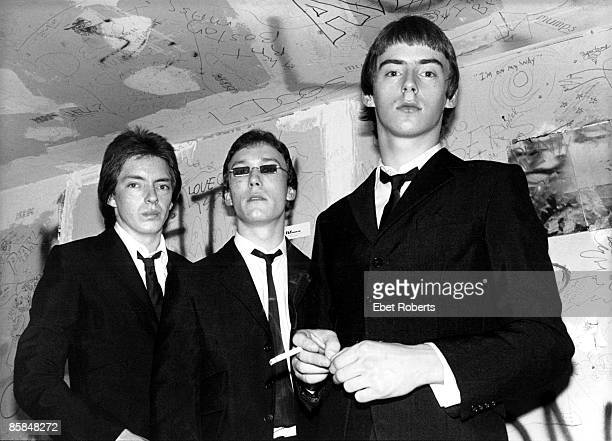 LR Bruce Foxton Rick Buckler Paul Weller of English punk band The Jam posed group shot in black suits backstage at CBGB's New York 15th October 1977