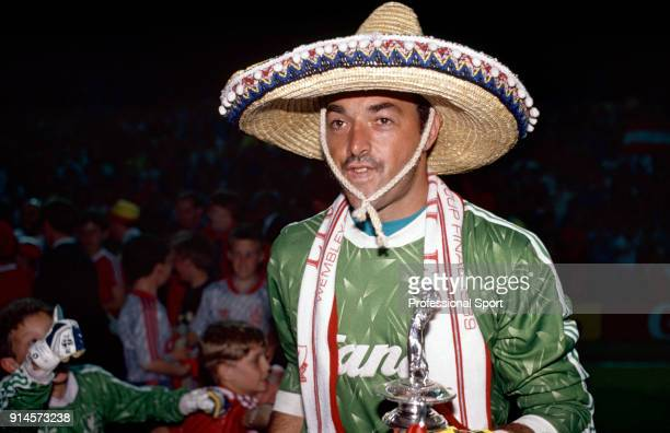 Bruce Grobbelaar of Liverpool celebrates with the League Championship trophy circa May 1990
