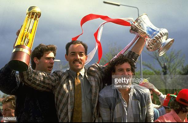 Bruce Grobbelaar of Liverpool holds the FA Cup and the Canon Division One trophy flanked by Jim Beglin and Craig Johnston during their homecoming...