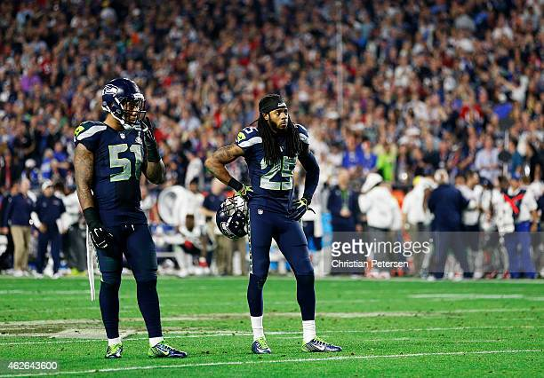 Bruce Irvin and Richard Sherman of the Seattle Seahawks react after losing to the New England Patriots during Super Bowl XLIX at University of...