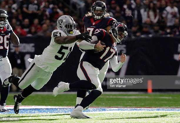 Bruce Irvin of the Oakland Raiders tackles Brock Osweiler of the Houston Texans during the first quarter of their AFC Wild Card game at NRG Stadium...
