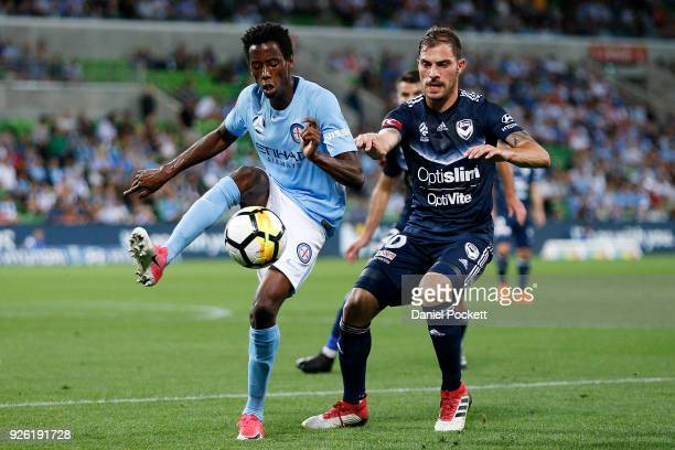 Bruce Kamau of Melbourne City contests the ball with James Troisi of the Victory during the round 22 ALeague match between Melbourne City FC and...