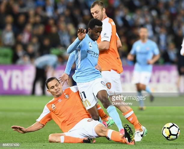 Bruce Kamau of the City is tackled by Jade North of the Roar during the round one ALeague match between Melbourne City FC and the Brisbane Roar at...