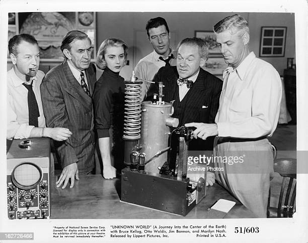 Bruce Kellogg Jim Bannon Marilyn Nash Tom Handley and Otto Waldis looking at device in laboratory in a scene from the film 'Unknown World' 1951