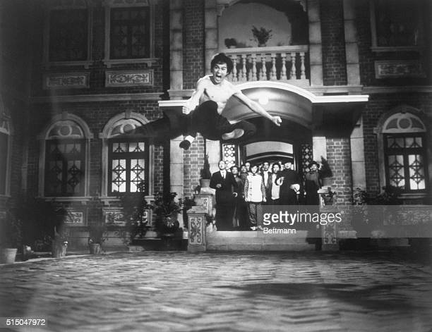 Bruce Lee demonstrating a Kungfu kick in the air as people watch on the set of The Chinese Connection Undated photo