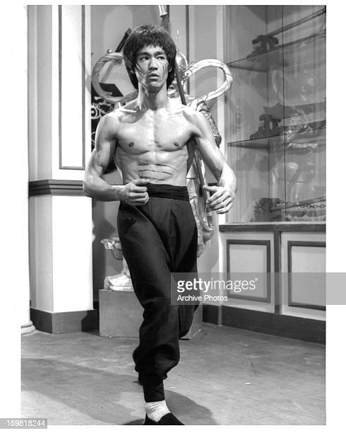 Bruce Lee shirtless running through a museum in a scene from the film 'Enter The Dragon' 1973