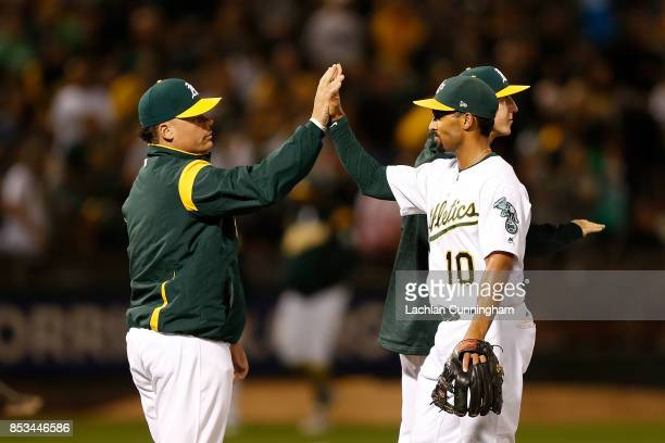 Bruce Maxwell of the Oakland Athletics celebrates with Marcus Semien after a win against the Texas Rangers at Oakland Alameda Coliseum on September...