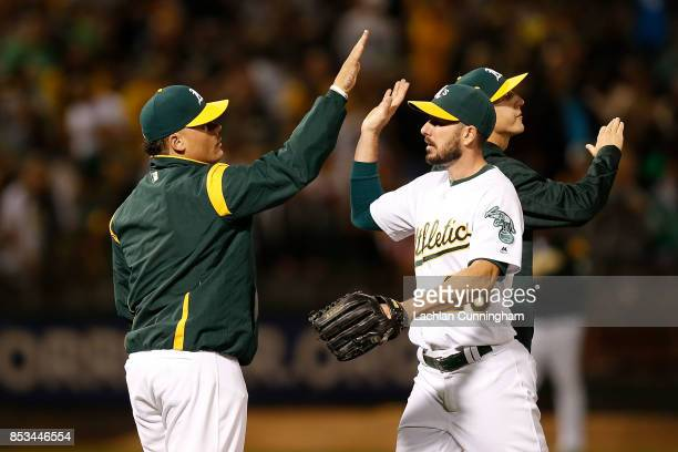 Bruce Maxwell of the Oakland Athletics celebrates with Matt Joyce after a win against the Texas Rangers at Oakland Alameda Coliseum on September 23...