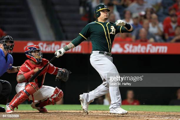 Bruce Maxwell of the Oakland Athletics hits a tworun homerun as Martin Maldonado of the Los Angeles Angels looks on during the fourth inning of a...