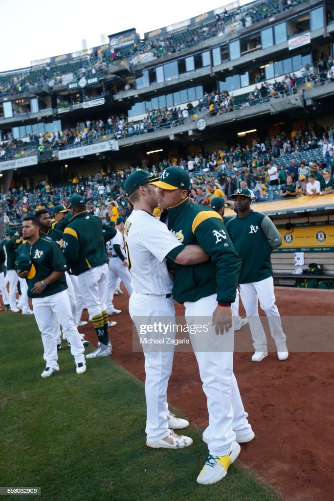 Bruce Maxwell #13 (R) of the Oakland Athletics is embraced after kneeling during the national anthem prior to the game against the Texas Rangers at the Oakland Alameda Coliseum on September 23, 2017 in Oakland, California. The Athletics defeated the Rangers 1-0.