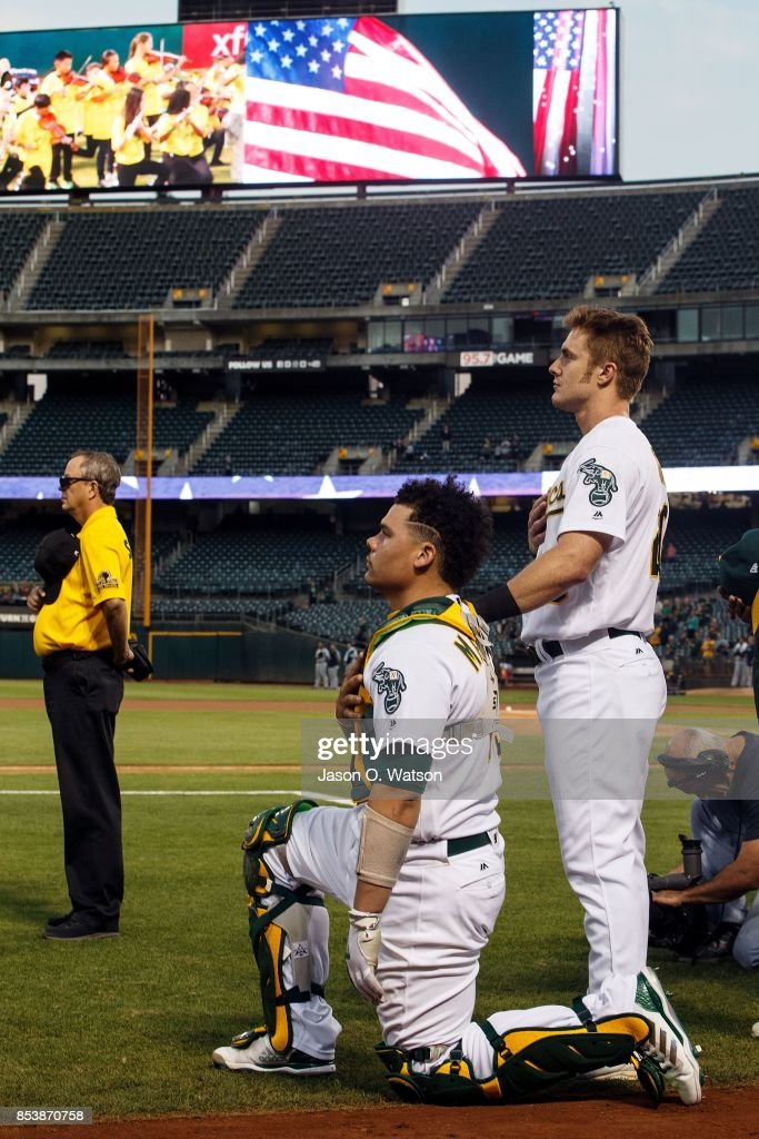 Bruce Maxwell #13 of the Oakland Athletics kneels during the national anthem in front of teammate Mark Canha #20 before the game against the Seattle Mariners at the Oakland Coliseum on September 25, 2017 in Oakland, California.